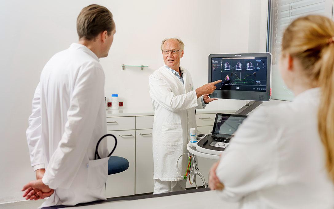 Dr. med. Reinhard Jochheim zeigt etwas am Monitor im medizinischen Versorgungszentrum für Kardiologie Jochheim Medizin in Hattingen